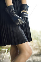Teen girl wearing gloves  hands clasped in front of her  cropped