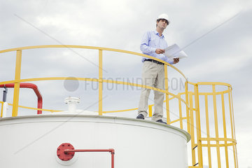 Engineer reviewing plans at industrial plant