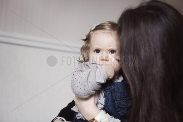 Mother comforting sulky baby girl