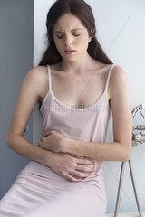 Woman sitting in bathroom clutching stomach