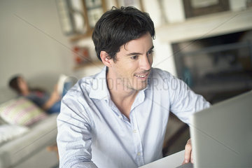 Man using laptop computer in living room