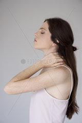 Woman rubbing neck  side view