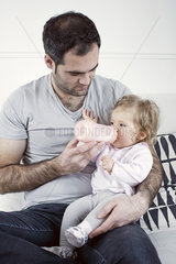 Father holding baby girl on lap  feeding her with bottle