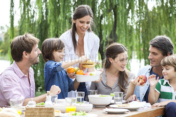 Family eating healthy meal together outdoors
