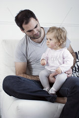 Father holding baby girl on lap
