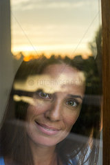 Woman looking through window at camera  portrait