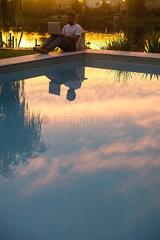 Man using laptop next to hotel swimming pool