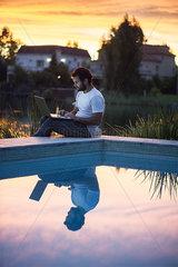 Man using laptop computer next to swimming pool as sun sets