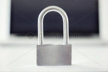 Close-up of padlock with laptop computer in background
