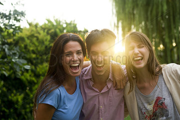 College friends having laughs together in park