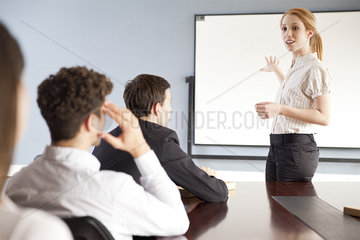 Businesswoman giving presentation at corporate meeting