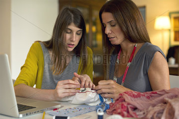Mother and daughter doing embroidery together