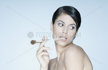 Woman holding make-up brush in mouth  portrait