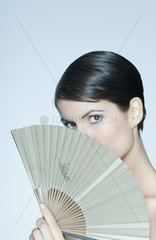 Woman holding fan in front of her face  portrait