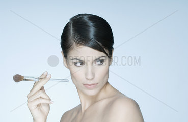 Woman holding make-up brush  looking away