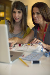 Mother and daughter learning embroidery together by watching online videos
