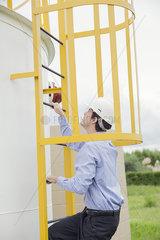 Engineer climbing storage tank ladder at industrial site