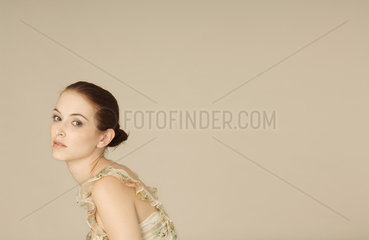 Young woman looking over shoulder sadly  portrait