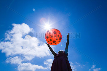 A young girl playing with a red spotted beach ball as she stands silhouetted against a deep blue sky and bright sunshine while throwing and catching the ball.