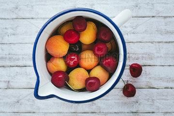 Aprikosen und Kirschen in einer Kanne