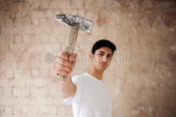 Junger Mann auf einer Baustelle zeigt einen Hammer