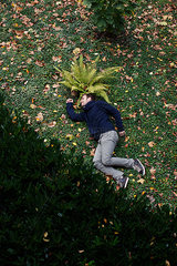 Mann in liegender Pose auf dem Rasen in einem Park