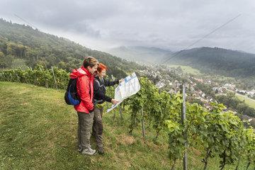 Zwei Wanderinnen orientieren sich in den Weinbergen