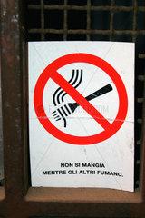 Mann isst nicht waehrend die andere Rauchen.