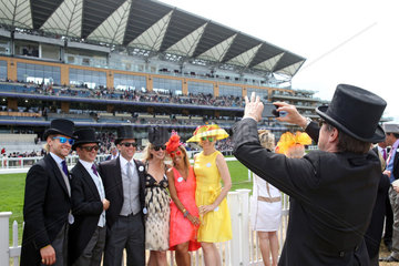 Royal Ascot  Man with top hat takes a picture of his friends standing in front of the grandstand