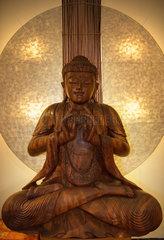 Berlin  Deutschland  Buddha aus Holz vor Lichtkreis