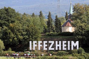 Iffezheim  Deutschland  Pferde und Jockeys unter dem Iffezheim-Schriftzug und der Kapelle