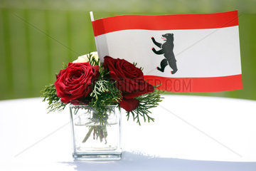 Hoppegarten  Deutschland  Fahne des Bundeslandes Berlin und rote Rosen in einer kleinen Vase