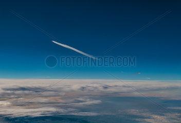 Flugzeug mit Kondensstreifen ueberfliegt die Alpen