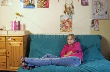 Pubertierendes Maedchen mit 13 Jahren langweilt sich in ihrem Zimmer