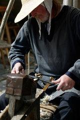 Altdorf  Deutschland  ein Mitwirkender im authentischen Kostuem schnitzt Holz