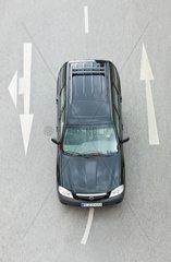 Auto von oben zwischen Fahrbahn-Richtungspfeilen -