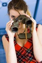 junge blonde Frau schaut durch ein Fernglas