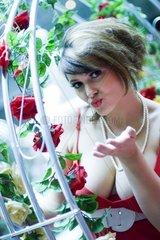 attraktive bruenette Frau wirft jemanden einen Kuss zu