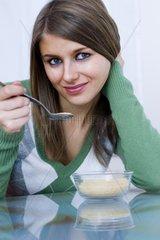 huebsche blonde Frau in gruenem Pulli isst laechelnd ein Dessert