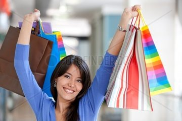 Shopping woman smiling in a mall with some bags