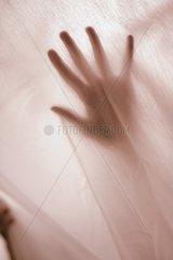 Frauenhand hinter einer Gardine