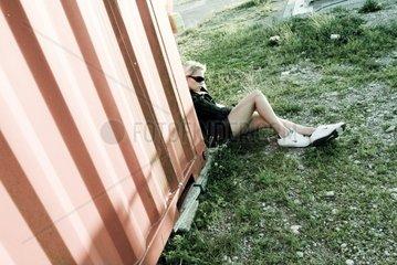 drogensuechtige Frau liegt neben Container