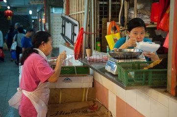 Singapur  Republik Singapur  Zwei essende Fleischverkaeuferinnen in Chinatown