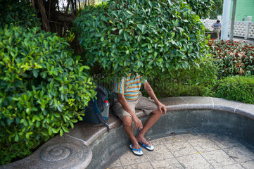 Singapur  Republik Singapur  Mann unter einem Baum