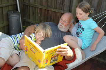 Arnis  Deutschland  ein Grossvater liegt mit seinen Enkeln in der Haengematte