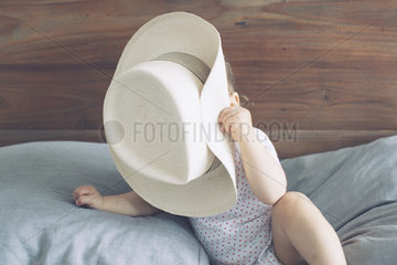 Baby with face obscured by oversized hat