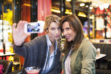Women in bar taking self-portrait with photophone
