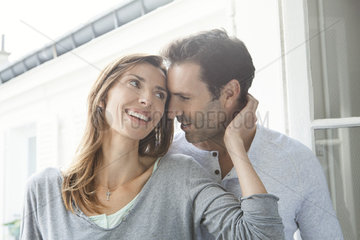 Couple whispering and smiling by window