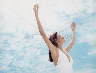 Woman standing outdoors with arms raised  eyes closed  low angle view