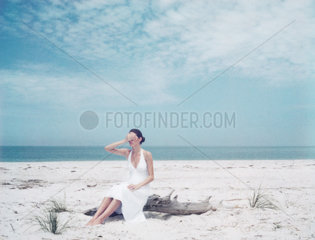 Woman sitting on driftwood at the beach  hand covering eyes